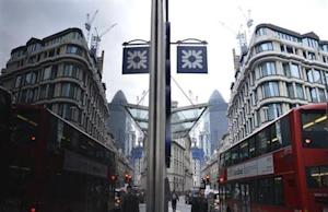 A logo from a Royal Bank of Scotland branch is seen reflected in a window in the City of London