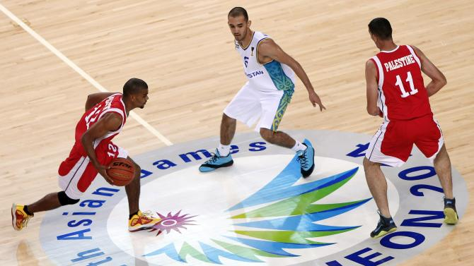 Palestinian Ibrahim Aburahal dribbles past Kazakhstan's Murzagaliyev during their men's basketball qualifying game during 17th Asian Games in Incheon