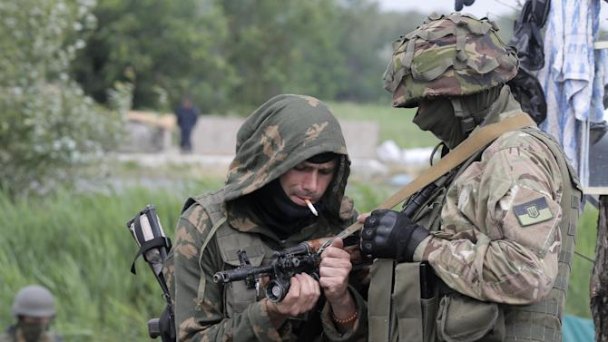 Ukrainian soldiers prepare their weapons at a position in Slovyansk, Ukraine, Saturday, May 31, 2014. The Ukrainian Acting Defense Minister said on Friday that troops had ousted separatists from southern and western parts of the Donetsk region and north of the Luhansk region. (AP Photo/Efrem Lukatsky)