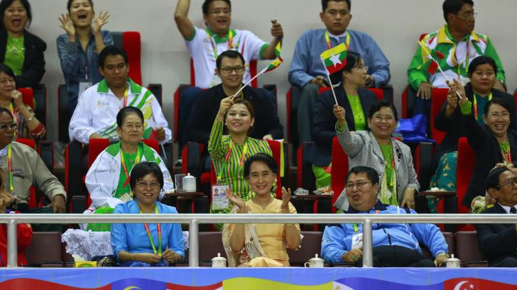 Aung San Suu Kyi claps as she watches the Sepaktakraw match between Thailand and Myanmar during the 27th SEA Games in Naypyitaw