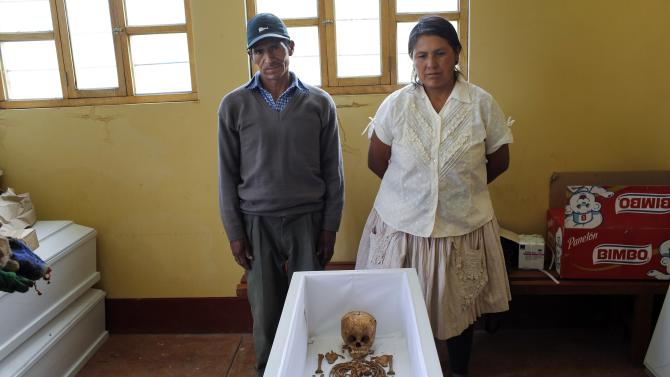 In this Nov. 25, 2015 photo, Julian Quispe Huallpa and his wife Lidia Quispe, pose for a photo next to the exhumed remains of their 3-year-old niece Necisa Curo Quispe, after forensic anthropologists arranged her skeletal remains in the coffin, in Valle Esmeralda de Huayao, Peru. Necisa Curo Quispe was killed in 1992, as Shining Path guerrillas surrounded the town and slaughtered men, women, children and the elderly. (AP Photo/Rodrigo Abd)