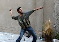 A rebel fighter throws a handmade hand grenade towards pro-Syrian government troops during fighting in the Bustan al-Bashar district of the northern Syrian city of Aleppo