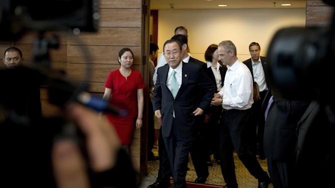 U.N. Secretary-General Ban Ki-moon, center, walks out from a room to take questions from the journalists after he visited the China National Low Carbon Day Exhibition at the Capital Museum in Beijing, China Thursday, June 20, 2013. Ban on Thursday expressed outrage over Wednesday's attack by al-Qaida-linked militants to the U.N. compound in the Somali capital of Mogadishu, which killed at least 13 people. (AP Photo/Andy Wong)