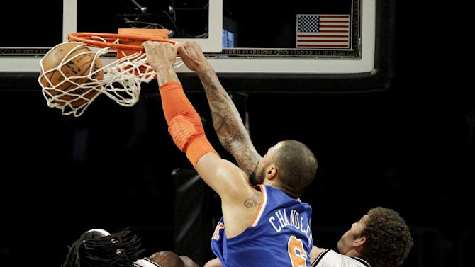 New York Knicks center Tyson Chandler (6) dunks over Brooklyn Nets forward Gerald Wallace (45) and center Brook Lopez (11) in the first half of their NBA basketball game at Barclays Center, Monday, Nov. 26, 2012, in New York. (AP Photo/Kathy Willens)
