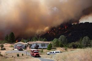 """Firefighters protect an evacuated home while the """"Sand Fire"""" burns behind, near Plymouth, California"""