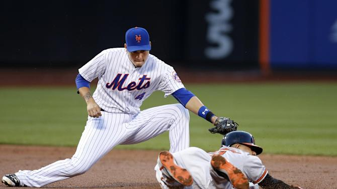 New York Mets shortstop Wilmer Flores (4) prepares to apply the tag, but Baltimore Orioles Manny Machado is safe on a second-inning stolen base in a baseball game in New York, Wednesday, May 6, 2015. (AP Photo/Kathy Willens)