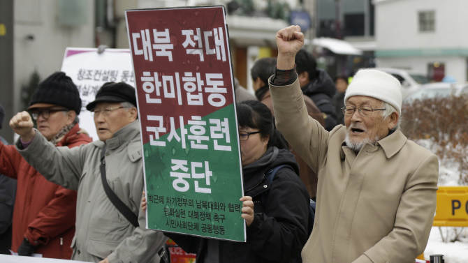 """Protesters shout slogans during a rally denouncing the joint military exercises between South Korea and the United States in front of the transition team office for President-elect Park Geun-hye in Seoul, South Korea, Tuesday, Feb. 5, 2013. South Korean and U.S. troops began naval drills Monday in a show of force partly directed at North Korea amid signs that Pyongyang will soon follow through on a threat to conduct its third atomic test. The letters read """" Stop, Joint military exercises between South Korean and the United States.""""  (AP Photo/Lee Jin-man)"""