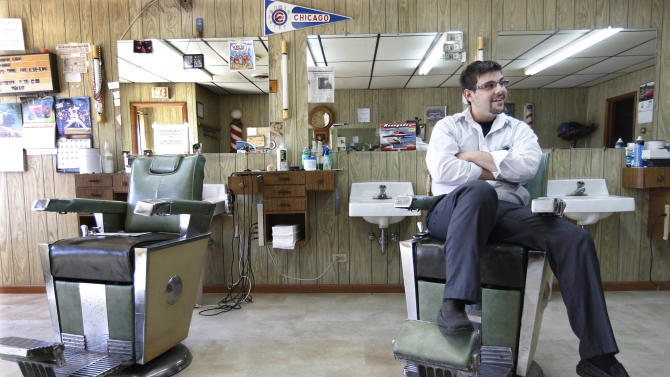In this Wednesday, April 11, 2012 photo, Alexander Skoutaris, 24, a barber at Al's Barber Shop in Crete, Ill., for the past three years, discusses the controversy surrounding the community's consideration of a proposal by U.S. Immigration and Customs Enforcement and a private company to build a nearly 800-bed immigrant detention facility just outside of town. The plan could be stopped if a measure in the Illinois Legislature which extends the state's ban on privately-contracted jails, passes the state House in the coming weeks. Many residents of this historical small town dating back to the days when its main street, now the Dixie Highway, was a buffalo trail and a fur trading route followed by Native Americans and early settlers, oppose the idea. Change comes slow in cities like Crete; in its 80 years of business, Al's Barber Shop has never had a phone. (AP Photo/M. Spencer Green)