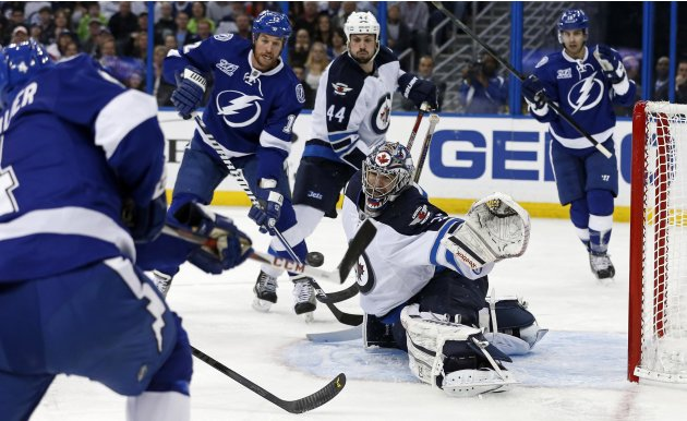 Winnipeg Jets goalie Montoya prepares to make a save on a shot by Tampa Bay Lightning's Lecavalier as Malone and Bogosian look on during their NHL hockey game in Tampa, Florida