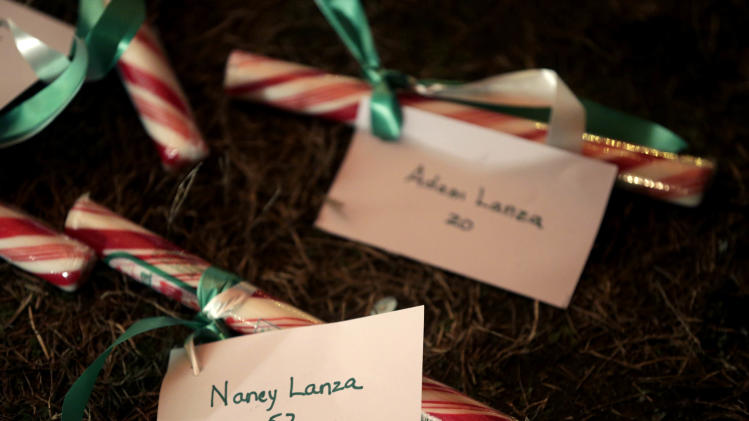 FILE - In this Thursday, Dec. 20, 2012, file photo, the names of Nancy Lanza and Adam Lanza are attached to candy at a memorial to the Newtown shooting victims in Newtown, Conn. Thousands of pages of documents from the Newtown shooting investigation help fill out the picture of Nancy Lanza as a dedicated and loving, if bewildered, parent who acknowledged her son Adam appeared to be spiraling downward but was not aware to what extent. On Dec. 14, 2012, Adam fatally shot her in her bed, gunned down 20 first-graders and six educators at Sandy Hook Elementary School in one of the worst mass shootings in the nation's history, and killed himself with a handgun as police closed in. (AP Photo/Seth Wenig, File)