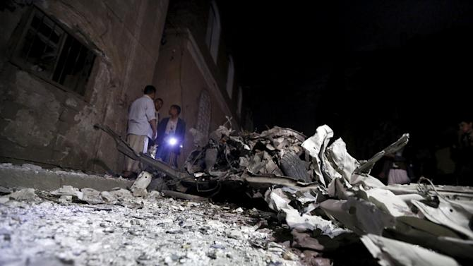 People stand next to wreckage at the site of a car bomb attack in Yemen's capital Sanaa