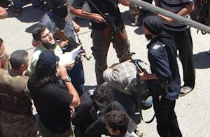 Rebel fighters prepare to execute two men, on July …