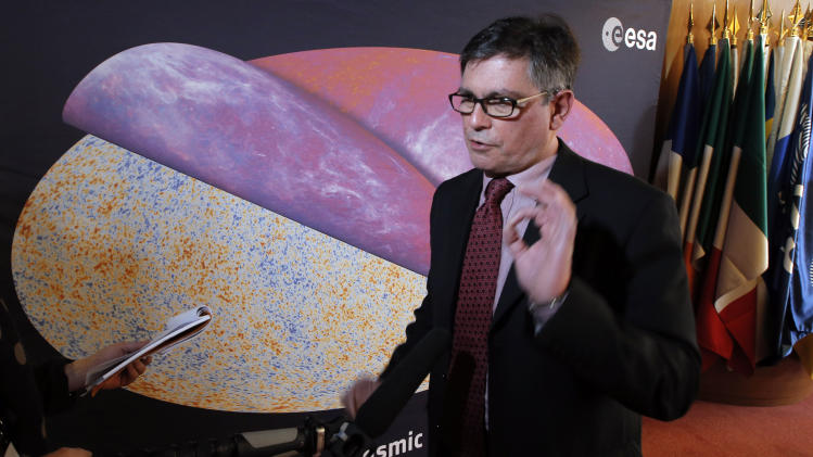 George Efstathiou, a European Space Agency astrophysicist speaks to The Associated Press after the press conference at ESA headquarters, in Paris, Thursday, March 21, 2013 in front of the most detailed map ever created of the cosmic microwave background acquired by ESA's Planck space telescope. Efstathiou, who announced the Planck satellite mapping on Thursday, says the findings also offer new specificity of the universe's composition. (AP Photo/Francois Mori)