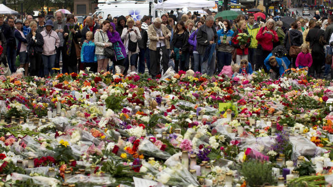 People look at tributes in memory of the victims of the attacks on Norway's government headquarters and an island youth retreat, as they pay their respects outside Oslo Cathedral, Sunday, July 24, 2011.   A Norwegian man detonated a bomb in central Oslo and then gunned down at least 84 people at Utoya island youth retreat, on Friday before being arrested.  (AP Photo/Matt Dunham)