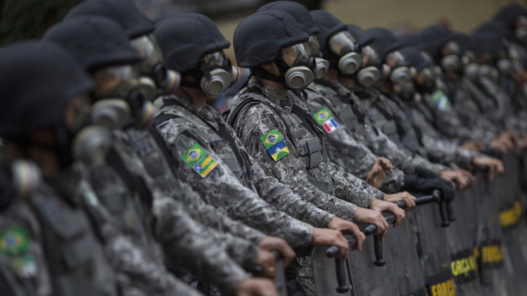 Federal police in riot gear stand guard outside Maracana stadium where protesters are gathered in Rio de Janeiro, Brazil, Sunday, June 30, 2013. Anti-government protesters are marching Sunday near the Maracana football stadium before a major international match, venting their anger about the billions of dollars the Brazilian government is spending on major sporting events rather than public services. (AP Photo/Felipe Dana)