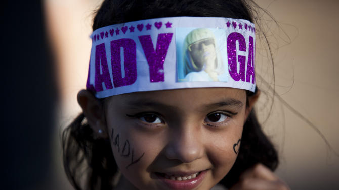 """A Lady Gaga fan smiles for a photo as she stands outside, waiting to enter the stadium where the U.S. pop star will perform a concert, in Buenos Aires, Argentina, Friday, Nov. 16, 2012. The Latin American leg of her, """"Born This Way Ball Tour,"""" is coming to an end but not before stopping in Chile, Peru and Paraguay. (AP Photo/Natacha Pisarenko)"""