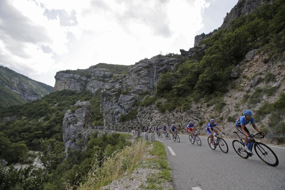 The pack rides through Meouge canyon during the sixteenth stage of the Tour de France cycling race over 168 kilometers (105 miles) with start in in Vaison-la-Romaine and finish in Gap, France, Tuesday July 16, 2013. (AP Photo/Christophe Ena)