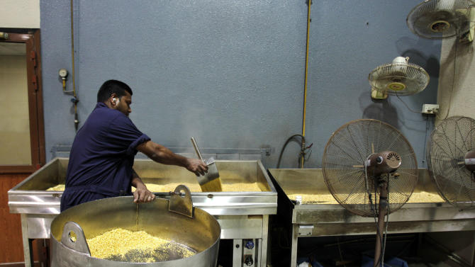 In this Monday Oct. 29, 2012 photo, steam rises from hot grains of gold after being melted and dropped into water as a technician pours the nuggets into a cooling container at the Emirates Gold company in Dubai, United Arab Emirates. One of the largest gold factory in the region, Emirates Gold  has processed more than two million kg of gold, worth about 108 billion U.S. dollars, into gold bars, coins and medals since it was established in 1992, Mohamad Shakarchi, managing director of the company says. (AP Photo/Kamran Jebreili)