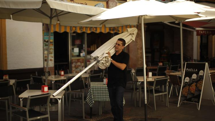 "Mesa, a first-year nursing student who has been hired as a temporary waiter since last July, carries an umbrella in the terrace of the ""La Terminal"" restaurant in downtown Ronda,"