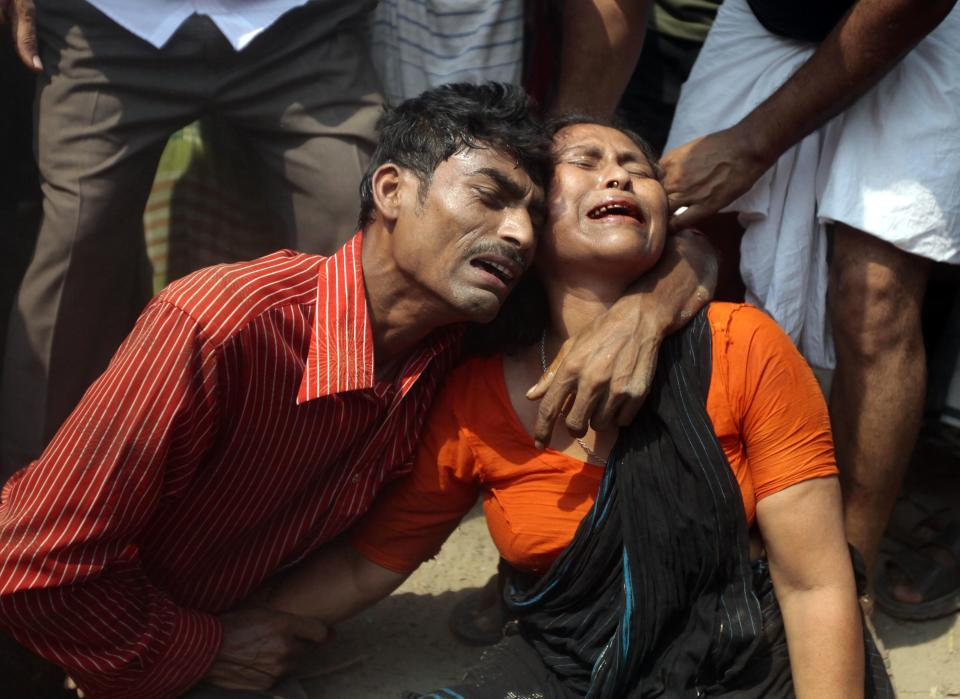 Relatives mourn a victim at the site where an eight-story building housing several garment factories collapsed in Savar, near Dhaka, Bangladesh, Wednesday, April 24, 2013.  The building collapsed near Bangladesh's capital Wednesday morning, killing dozens of people and trapping many more in the rubble, officials said. (AP Photo/ A.M. Ahad)