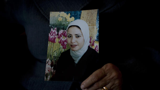 In this photo taken Saturday, Feb. 1, 2014, Palestinian Khadra al-Akhras poses with a photo of her late daughter Ayat al-Akhras who blew herself up in a suicide bombing outside a Jerusalem supermarket in 2002, at the family house in the West Bank city of Bethlehem. More than a decade later, after appeals from human rights groups, Israel is handing over some 30 bodies of Palestinian assailants, including that of Ayat. (AP Photo/Nasser Nasser)
