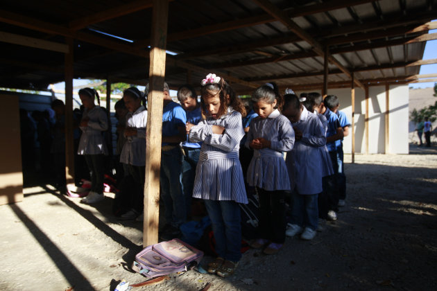 Palestinian Bedouin Students pray at their school at Khan al-Ahmar, near the west bank city of Jericho, Sunday, Sept 2. 2012. Dozens of Palestinian children in the ramshackle Bedouin community outside