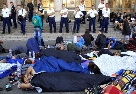 Migrants rest outside the main Eastern Railway station in Budapest