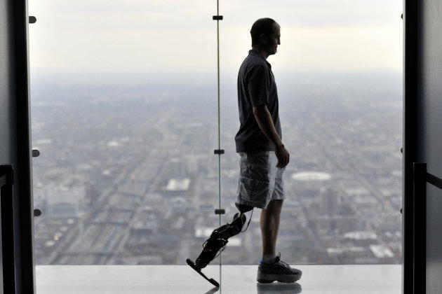 "In this Oct. 25, 2012 photo, Zac Vawter, fitted with an experimental ""bionic"" leg, is silhouetted on the Ledge at the Willis Tower in Chicago. Vawter is training for the world's tallest stair-climbing event where he'll attempt to climb 103 flights to the top of theWillis Tower using the new prosthesis. (AP Photo/Brian Kersey)"