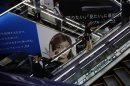 Shoppers pass an advertisement of Sony Corp. as they ride on escalators at an electronics store in Tokyo