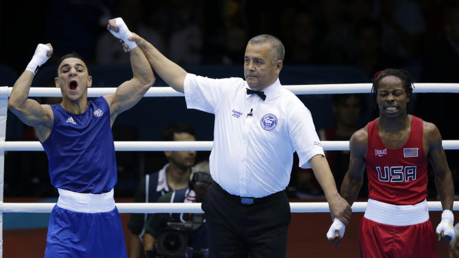 France's Nordine Oubaali, left, reacts after defeating the United States' Warren Raushee in a men's flyweight 52-kg preliminary boxing match at the 2012 Summer Olympics, Friday, Aug. 3, 2012, in London. (AP Photo/Ng Han Guan)
