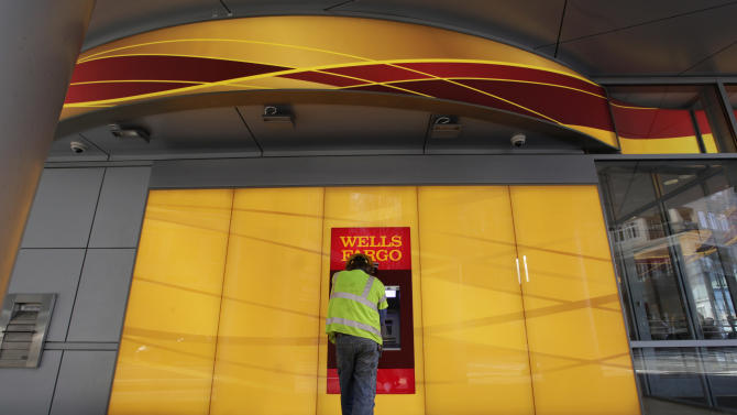 A customer uses an ATM outside a Wells Fargo branch in Charlotte, N.C., Tuesday, Jan. 17, 2012. Wells Fargo & Co. reports their company earnings on Friday, July 12, 2013. (AP Photo/Chuck Burton)