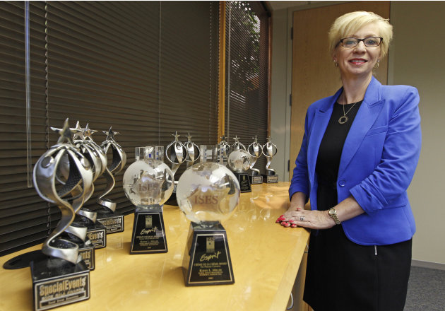 In this Friday, June 15, 2012 photo, Kathy Miller, president of Total Event Resources, poses for a photograph next to trophies awarded to her company in her offices in Schaumburg, Ill. In 2008, her ev