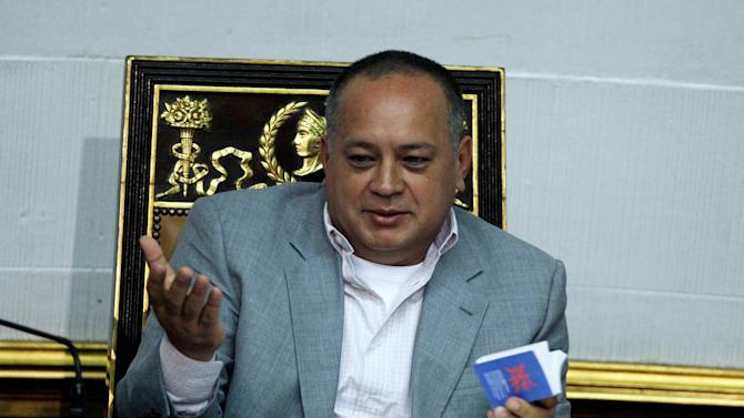 Venezuela's National Assembly President Diosdado Cabello gestures as he holds a copy of the Venezuelan Constitution during a session in Caracas, Venezuela, Tuesday, Jan. 8, 2013. President Hugo Chavez won't be able to attend his scheduled swearing-in this week, Venezuela's government announced, confirming suspicions that the leader's illness will keep him in a Cuban hospital past the key date. (AP Photo/Fernando Llano)