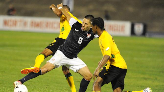 United States' Clint Dempsey, center, fights for the ball with Jamaica's Jason Morrison, left, and Ryan Johnson during a 2014 World Cup qualifying soccer match in Kingston, Jamaica, Friday, Sept. 7, 2012. Jamaica won 2-1. (AP Photo/Collin Reid)