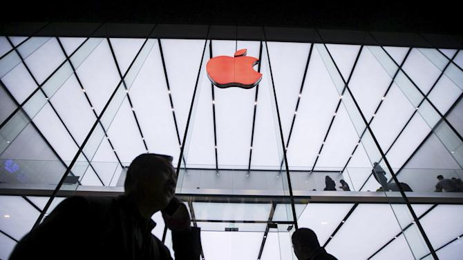People walk past below an Apple logo in red marking the World AIDS Day, at an Apple store in Hangzhou