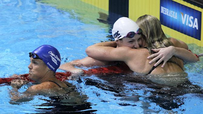 Dara Torres, left, looks at the results after swimming in the women's 50-meter freestyle final at the U.S. Olympic swimming trials as Kara Lynn Joyce and Jessica Hardy, right, celebrate, Monday, July 2, 2012, in Omaha, Neb. (AP Photo/Nati Harnik)