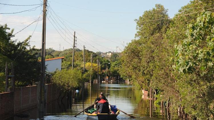 People transport their belongings on a small boat in a flooded neighborhood in Asuncion, on June 10, 2014