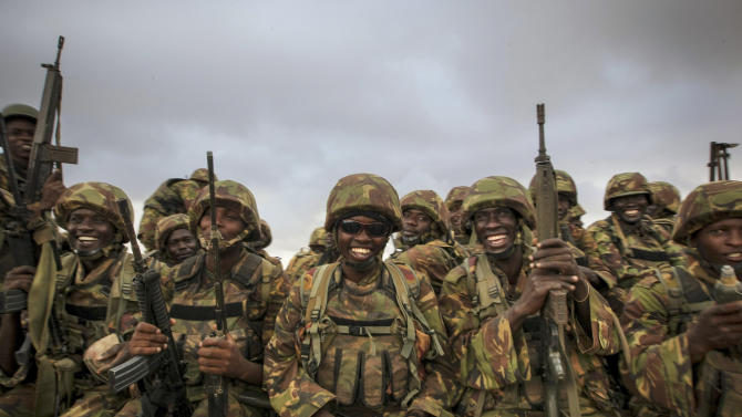 In this photo taken Tuesday, Oct. 2, 2012 and released by the African Union-United Nations Information Support Team on Wednesday, Oct. 3, 2012, Kenyan soldiers serving with the African Union Mission in Somalia (AMISOM) sit on a flat-bed truck in the morning as they prepare to enter Kismayo, southern Somalia. Allied African troops have taken full control of Kismayo in Somalia, the last stronghold of al-Shabab Islamist rebels who have been fighting against the country's internationally backed government, a Kenyan military official said Tuesday, and Kenya Defence Forces and the Somali National Army are now patrolling the streets. (AP Photo/AU-UN IST, Stuart Price)