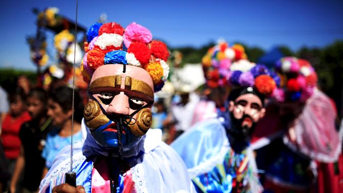 """Members of the traditional Los Historiantes dance group perform during a welcoming ceremony for Catholic devotees known as """"Cumpas"""", in the town of Cuishnahuat, El Salvador"""