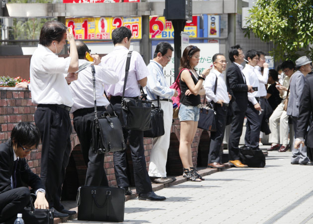 In this June 29, 2012 photo, Japanese office workers wait for their colleagues in front of a railway station in Tokyo. Government data showed Tuesday, July 31, Japan's unemployment rate for June improved slightly to 4.3 percent, declining for the second straight month, but the nation continues to struggle after last year's disaster. The Ministry of Internal Affairs and Communications reported that the jobless rate last month fell 0.1 percentage point from 4.4 percent in May. (AP Photo/Koji Sasahara)