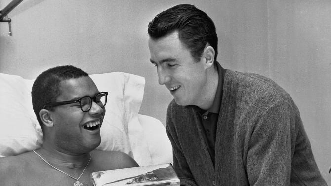 """FILE - In this Feb. 9, 1962 file photo, Jack Twyman, right, holds the trophies he and Maurice Stokes received from the Philadelphia Sports Writers Association designating them as the """"Most Courageous Athletes"""" in Stokes' hospital room in Cincinnati, Ohio. Twyman, a Basketball Hall of Famer, has died at 78. He was one of the NBA's top scorers in the 1950s who became the guardian to paralyzed teammate, Stokes. Jay Twyman, of Rye, N.Y., said Thursday, May 31, 2012 that his father died Wednesday, May 30 at a Cincinnati hospice of complications from an aggressive form of blood cancer. Jack Twyman played for the University of Cincinnati and spent 11 seasons in the NBA with the Rochester and Cincinnati Royals. (AP Photo)"""