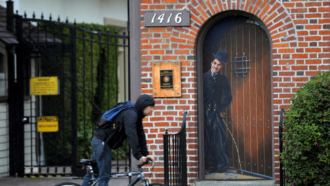 A bike rider passes an image of silent film legend Charlie Chaplin at the entrance to the Jim Henson Company Lot in Los Angeles, Wednesday, Feb. 15, 2012. The lot, initially built in 1918 for Charlie Chaplin Studios, is where many of Chaplin's  movies were filmed. (AP Photo/Chris Pizzello)