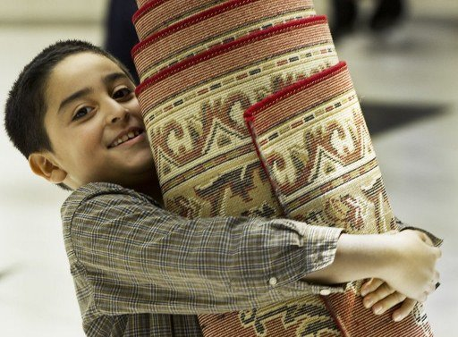 A young boy helps move prayer rugs for temporary  storage to use the area for the evening meal at the Dar al Hijra Mosque as Ramadan nears its end on August 10, 2012 in Falls Church, Virginia. Imam Shaker Elsayed condemned Syria's brutal crackdown on dissent and called on Muslims to raise funds for civilians trapped in the conflict.         AFP PHOTO/Paul J. Richards