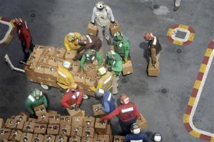Handout picture of air department sailors stacking relief supplies on the flight deck of USS George Washington in Philippine Sea