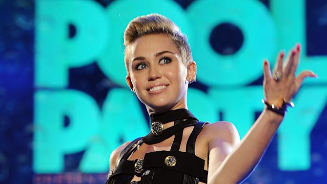 """FILE - This June 29, 2013 file photo shows Miley Cyrus hosting the iHeartRadio Ultimate Pool Party at the Fontainebleau Hotel in Miami. NBC said Monday, Sept. 9, that the singer and actress, who popularized the word """"twerking"""" and found new uses for foam fingers during an attention-getting duet with Robin Thicke on the MTV Video Music Awards last month, will be both host and musical guest of the NBC late-night program on Oct. 5. (Photo by Jeff Daly/Invision/AP, File)"""