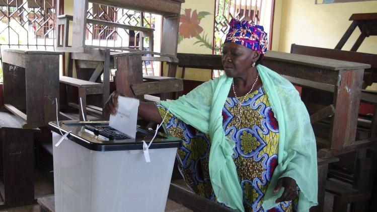 A woman casts her ballot at a polling station in Guinea's capital Conakry