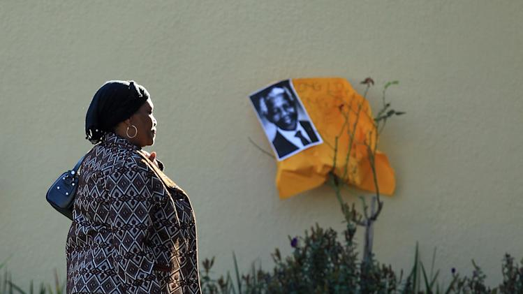 Unidentified woman walks past a get well message with a portrait of former President Mandela, outsdie his home in Johannesburg, South Africa, Sunday, June 16, 2013.  The 94-year old Mandela remains in the hospital for a ninth day for a recurring lung infection. (AP Photo/Themba Hadebe)