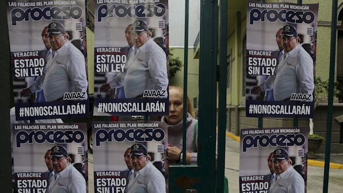A passerby looks at posters of Veracruz state governor Javier Duarte  during a demonstration against the murder of photojournalist Ruben Espinosa outside the Government of Veracruz building in Mexico City