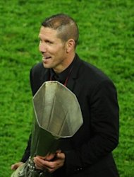Atletico Madrid's Argentinian coach Diego Simeone holds the trophy after his team won the UEFA Europa League final football match between Atletico Madrid and Athletic Bilbao at the National Arena stadium in Bucharest