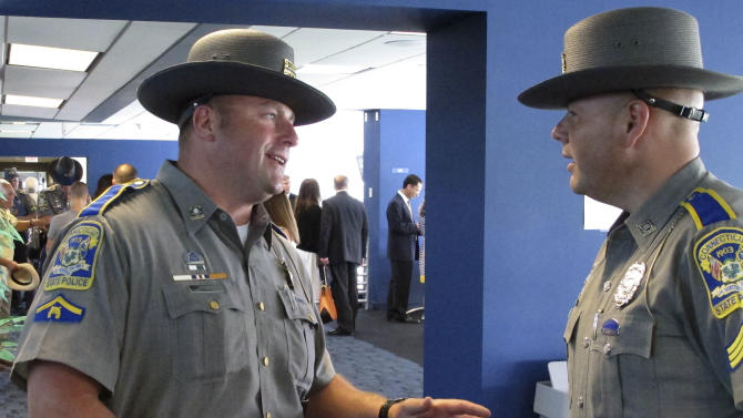 Connecticut state Trooper First Class Matthew Bell, left, talks with state police Sgt. Troy Anderson on Tuesday, July 8, 2014, in East Hartford, Conn., following a ceremony to honor first responders and others who helped in the aftermath of the Sandy Hook Elementary School shooting. Bell was among the first police officers to enter the school after 20 first-graders and six educators were shot to death in December 2012. Bell and Anderson, who runs the state police behavioral health programs, were among more than 300 people honored for outstanding and meritorious service. (AP Photo/Dave Collins)